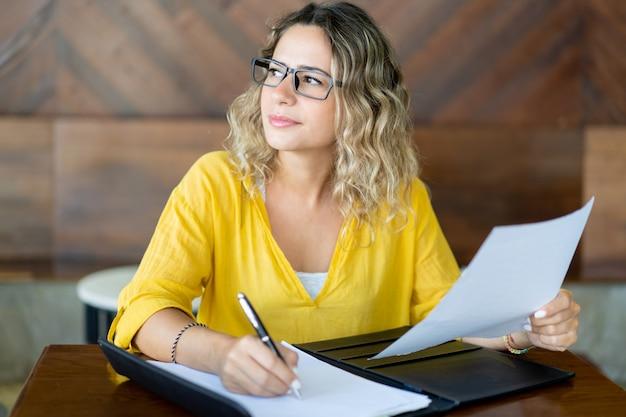 Hübscher weiblicher unternehmensleiter, der bei tisch bei dokumenten arbeitet