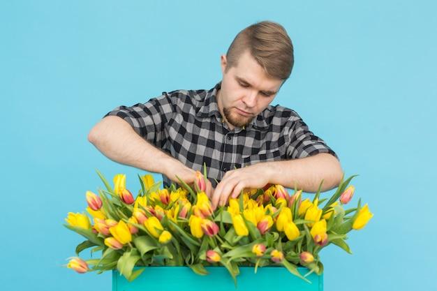 Hübscher weißer männlicher gärtner, der einen strauß tulpen im blauen studio macht.
