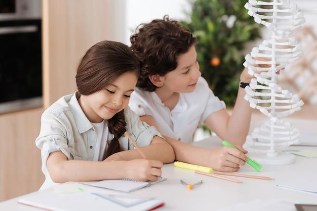 Hübscher, welliger junge, der ein großes weißes 3d-dna-modell untersucht und einen grünen textmarker in der hand hält, während seine kleine schwester die informationen niederlegt