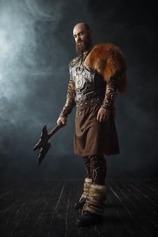 Hübscher wikinger mit axt gekleidet in traditioneller kleidung