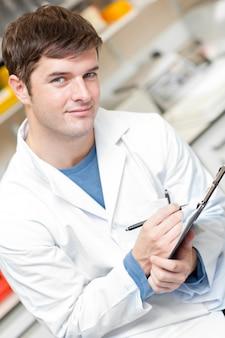 Hübscher wissenschaftler, der ein klemmbrett hält und an der kamera lächelt