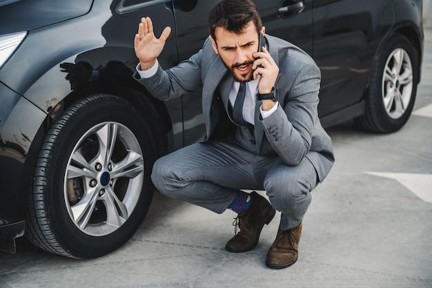 Hübscher wütender kaukasischer bärtiger geschäftsmann, der neben seinem auto kauert und dienst anruft.