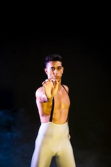 Hübscher zeitgenössischer tänzer, der im scheinwerferlicht durchführt