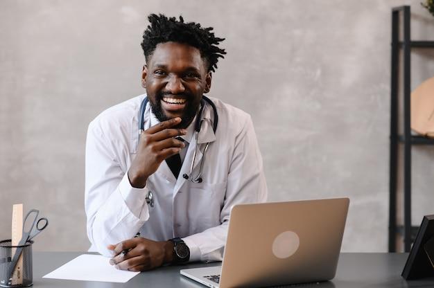 Hübscher zufriedener afroamerikanischer arzt, der an einem laptop arbeitet. telemedizin