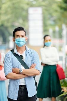 Hübscher zuversichtlicher junger vietnamesischer mann in der medizinischen maske, die draußen mit den gefalteten armen steht und kamera betrachtet