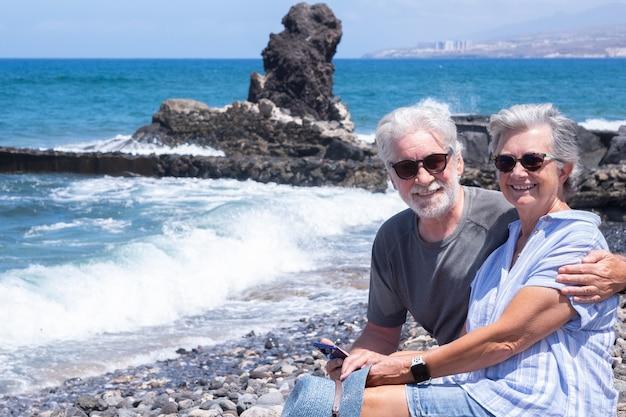 Hübsches älteres paar, das auf den felsen sitzt und kameralächeln betrachtet. zwei rentner genießen sommerferien und freiheit