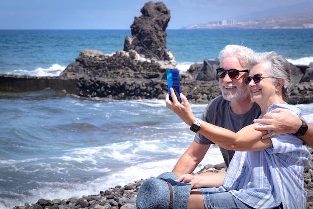 Hübsches älteres paar, das auf den felsen sitzt und lächelt und macht ein selfie. zwei rentner genießen sommerferien und freiheit