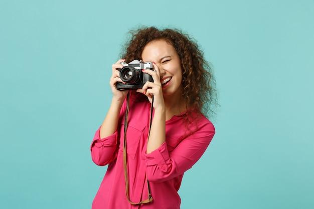 Hübsches afrikanisches mädchen in freizeitkleidung, das ein foto auf einer retro-vintage-fotokamera macht, die auf blau-türkisem wandhintergrund im studio isoliert ist. menschen aufrichtige emotionen lifestyle-konzept. kopieren sie platz.