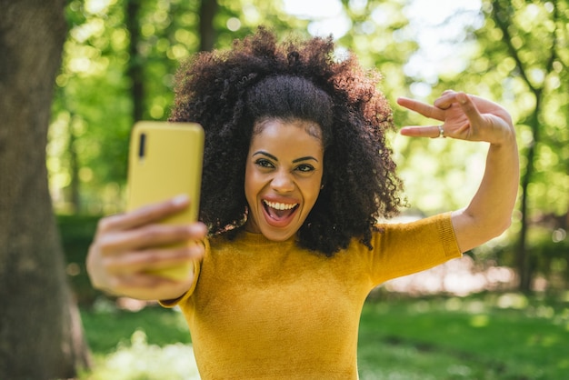 Hübsches afro-mädchen, das ein selfie macht und im wald lacht. selektiver fokus.