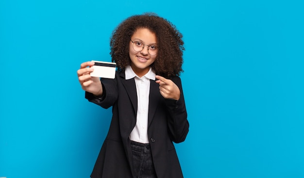 Hübsches afro-teenager-geschäftsmädchen mit einer kreditkarte. online-shopping-konzept