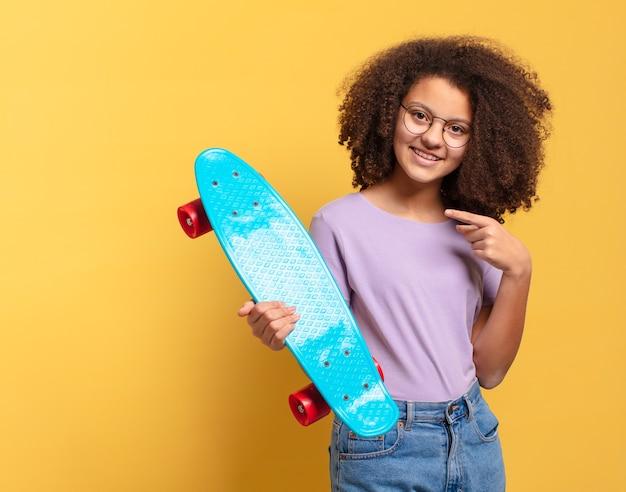 Hübsches afro-teenager-mädchen mit einem skateboard