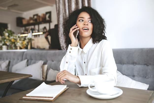 Hübsches afroamerikanisches mädchen, das im restaurant sitzt und auf ihrem handy spricht. junge dame im weißen hemd, das im café mit handy in der hand sitzt