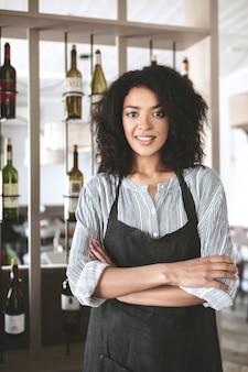 Hübsches afroamerikanisches mädchen in der schürze, die mit gefalteten händen im restaurant steht. junges mädchen mit dunklem lockigem haar, das in der schürze am café steht