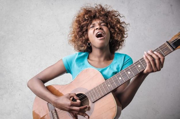 Hübsches afromädchen, das auf einer gitarre spielt