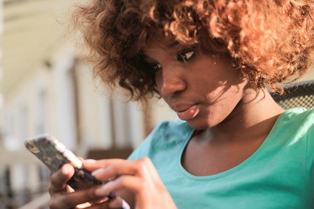 Hübsches afromädchen, das ihren smartphone überprüft