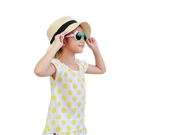 Hübsches asiatisches kind, das sonnenbrille und strohhut auf weiß trägt