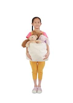Hübsches asiatisches kind des kleinen mädchens, das spielwarenbeutel für spende hält. kid halten tasche mit puppen auf weißem hintergrund. konzept des glücks an andere weitergeben und teilen