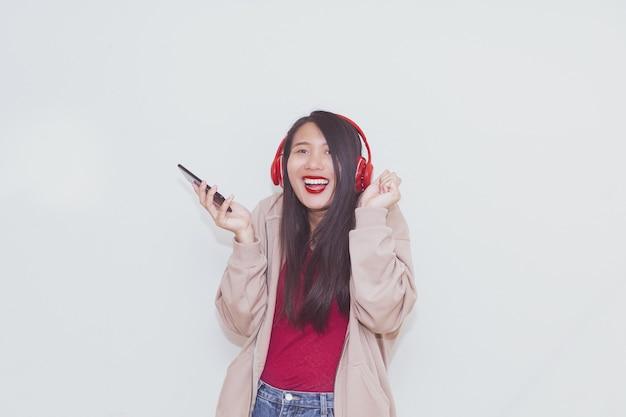 Hübsches asiatisches mädchen, das musik mit roten kopfhörern auf weißem hintergrund hört.