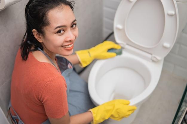 Hübsches asiatisches mädchen, das toilette im badezimmer putzt