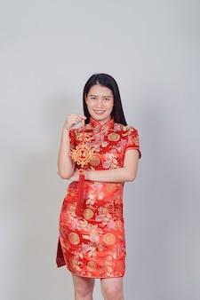 Hübsches asiatisches mädchen mit chinesischem traditionellem kleid cheongsam oder qipao, das feuerwerkskörper hält. chinesisches neujahrskonzept, weibliches modell isoliert im grauen studiohintergrund