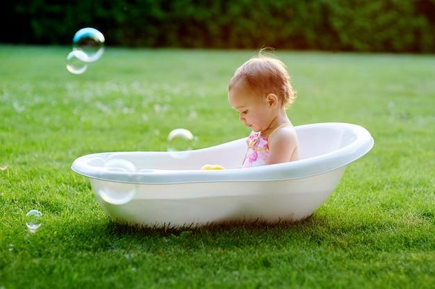 Hübsches baby, das draußen mit wasser in wenigem plastikbad im garten spielt