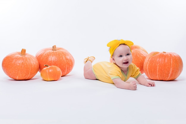Hübsches baby in einem gelben körper mit einem gelben bogen auf ihrem kopf