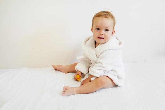 Hübsches baby mit einem weißen bademantel, nachdem ein bad genommen worden ist, das auf weißer abdeckung sitzt