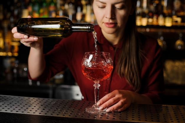 Hübsches barmannmädchen bereitet einen alkoholischen cocktail spritz veneziano zu
