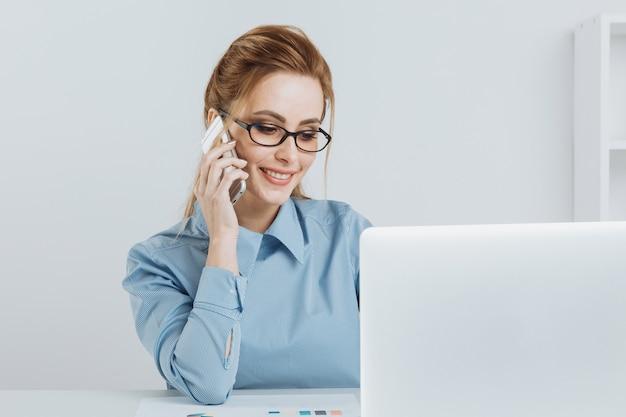 Hübsches blondes büromädchen, das telefon an ihrem arbeitsplatz spricht.