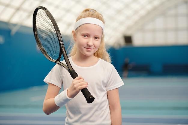 Hübsches blondes kleines mädchen in weißer activewear, das tennisschläger an der rechten schulter hält, während es in stadionumgebung vor der kamera steht