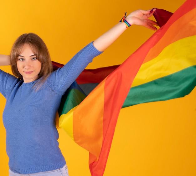 Hübsches blondes lesbisches mädchen mit schwuler stolzflagge auf pastellgelber wand