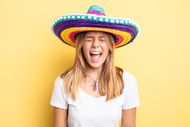 Hübsches blondes mädchen, das aggressiv schreit und sehr wütend aussieht. mexikanisches hutkonzept