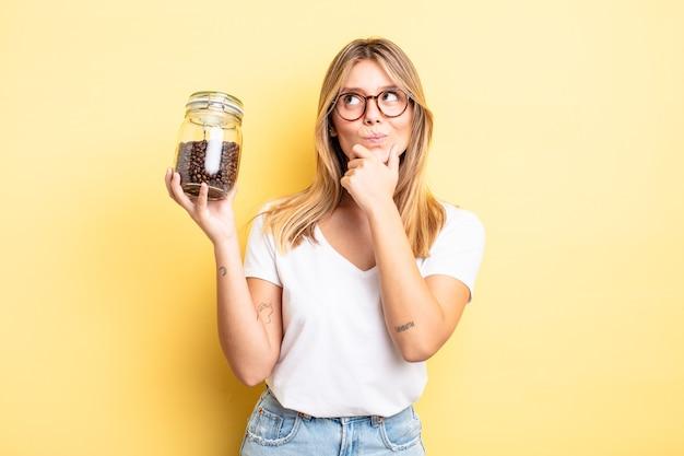 Hübsches blondes mädchen, das denkt, sich zweifelhaft und verwirrt fühlt. kaffeebohnen-konzept