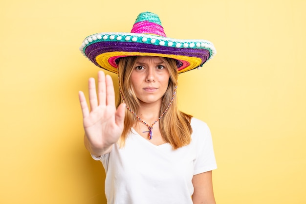Hübsches blondes mädchen, das ernste offene handfläche zeigt, die stoppgeste macht. mexikanisches hutkonzept