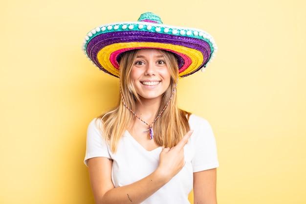Hübsches blondes mädchen, das fröhlich lächelt, sich glücklich fühlt und auf die seite zeigt. mexikanisches hutkonzept