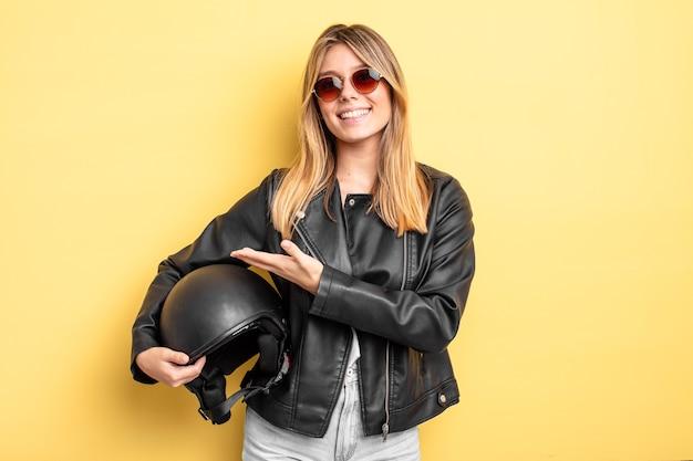 Hübsches blondes mädchen, das fröhlich lächelt, sich glücklich fühlt und ein konzept zeigt. motorradhelmkonzept