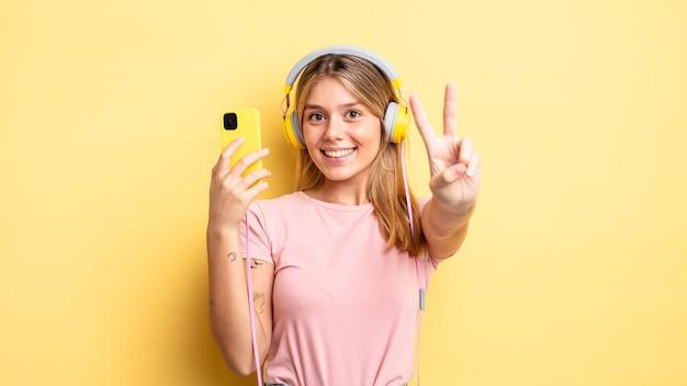 Hübsches blondes mädchen, das glücklich lächelt und schaut und sieg oder frieden gestikuliert. musikkonzept hören
