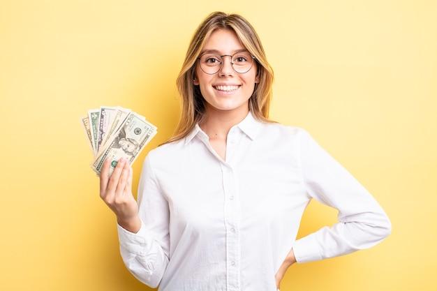 Hübsches blondes mädchen, das glücklich mit einer hand auf der hüfte lächelt und selbstbewusst ist. dollar-banknoten-konzept