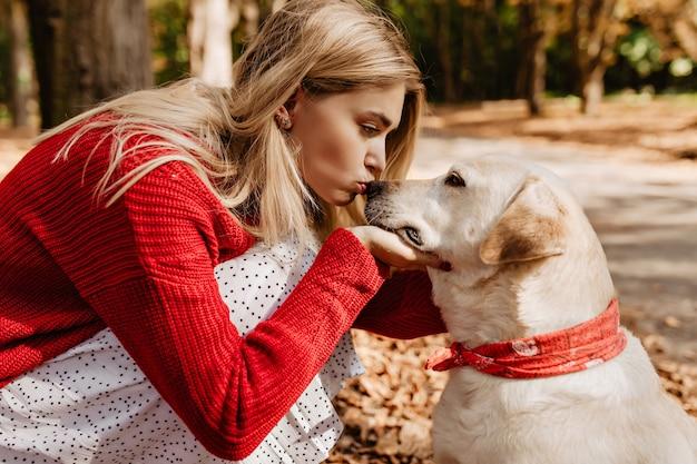 Hübsches blondes mädchen, das ihren schönen labradour küsst. junge frau, die rote farbe mit ihrem hund im herbstpark trägt.