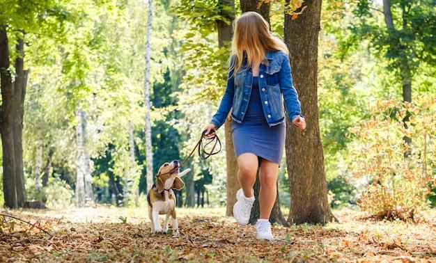 Hübsches blondes mädchen, das mit beagle-hund läuft