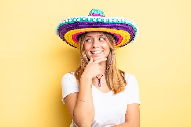 Hübsches blondes mädchen, das mit einem glücklichen, selbstbewussten ausdruck mit der hand am kinn lächelt. mexikanisches hutkonzept