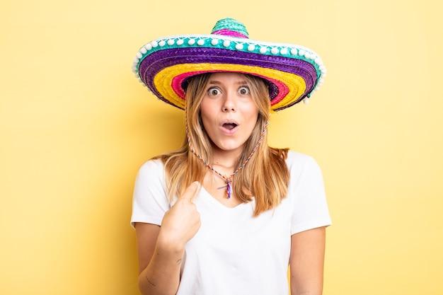 Hübsches blondes mädchen, das schockiert und überrascht mit weit geöffnetem mund aussieht und auf sich selbst zeigt. mexikanisches hutkonzept