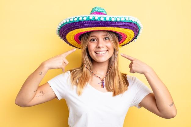 Hübsches blondes mädchen, das selbstbewusst lächelt und auf ein breites lächeln zeigt. mexikanisches hutkonzept