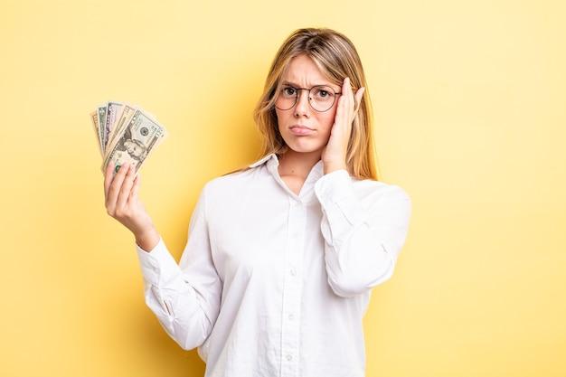 Hübsches blondes mädchen, das sich nach einer ermüdenden müdigkeit gelangweilt, frustriert und schläfrig fühlt. dollar-banknoten-konzept
