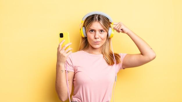 Hübsches blondes mädchen, das sich verwirrt und verwirrt fühlt und zeigt, dass sie verrückt sind. musikkonzept hören