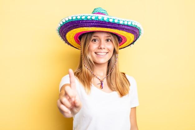 Hübsches blondes mädchen, das stolz und selbstbewusst lächelt und nummer eins macht. mexikanisches hutkonzept