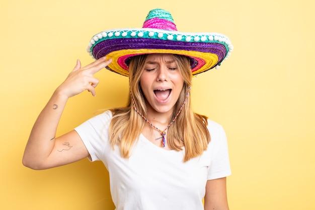 Hübsches blondes mädchen, das unglücklich und gestresst aussieht, selbstmordgeste, die waffenzeichen macht. mexikanisches hutkonzept