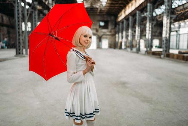 Hübsches blondes mädchen im anime-stil mit rotem regenschirm. cosplay mode, asiatische kultur, puppe im kleid, süße frau mit make-up im fabrikladen