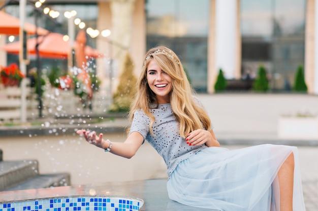 Hübsches blondes mädchen im blauen tüllrock, der spaß auf terrassenhintergrund hat. sie spritzte wasser und lächelte in die kamera.