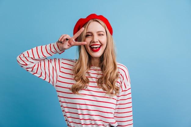 Hübsches blondes mädchen im gestreiften hemd, das friedenszeichen zeigt. vorderansicht der lachenden französischen dame, die auf der blauen wand aufwirft.